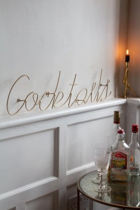 Side angle image of the Cocktails Typography Gold Metal Wall Art on a shelf