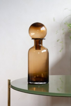 Lifestyle image of the Brown Glass Decanter Bottle with Ball Stopper