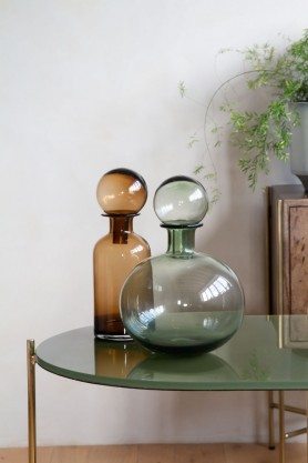 Lifestyle image of both the Glass Decanter Bottles With Ball Stopper on a table