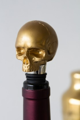 Front angle of the Gold Skull Bottle Stopper in a bottle