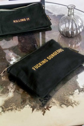 Lifestyle image of the Black Cotton Fucking Gorgeous Pouch Make Up Bag on a table