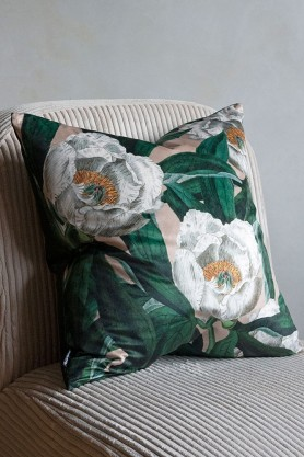Close-up image of the White Peony & Green Leaves Velvet Cushion sat on a chair