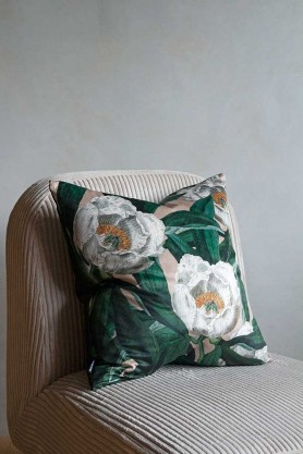 Image of the White Peony & Green Leaves Velvet Cushion sat on a chair