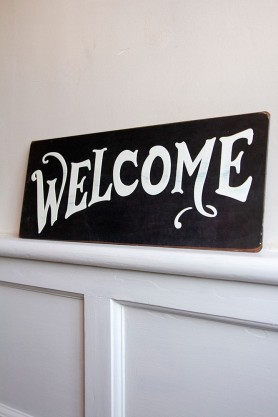 Image of the Vintage Metal Welcome Sign on a ledge