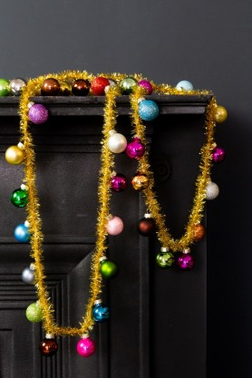 Image of the Rainbow Multicoloured Baubles & Tinsel Garland in rows on a fireplace
