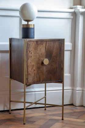 Lifestyle image of the Small Retro Mango Wood & Gold Bar Cabinet with a lamp