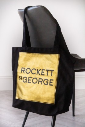 Close-up lifestyle image of the Rockett St George Gold Tote Bag hanging on the back of a chair