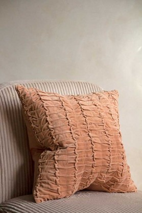 Image of the Peach Ruched Velvet Cushion on a chair