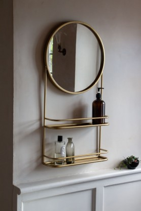 Lifestyle image of the Round Gold Mirror With Two Shelves