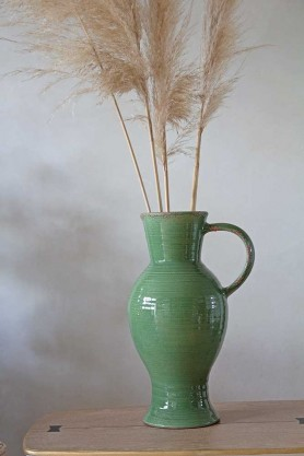 Lifestyle image of the Tall Green Glazed Jug Style Vase With Handle with pampass in it