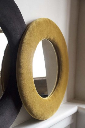 Lifestyle image of the Round Velvet Frame Mirror In Ochre Gold next to the Charcoal Grey version