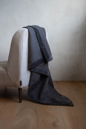 Lifestyle image of the Luxurious Waffle Throw with Velvet Edging In Charcoal Grey