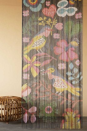 Lifestyle image of the Birds & Flowers Bamboo Door Curtain with rattan foot stool and cloisters painted wall background