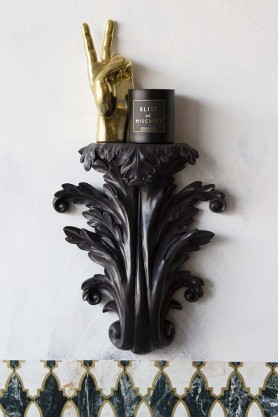 Lifestyle image of the Black Baroque Wall Sconce / Shelf on white wall background with candle and peace sign hand