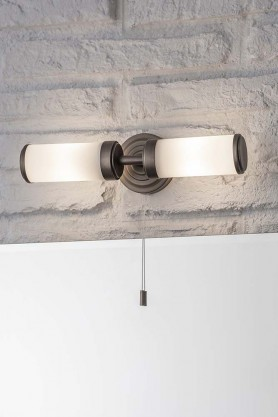 Lifestyle image of Bronze Beaufort Bathroom Wall Light switch on and fixed to a brick wall