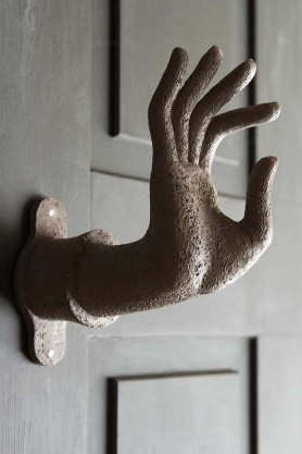 Lifestyle image of the Distressed Stone Effect Om Mudra Hand Wall Art / Coat Hook on dark painted door background