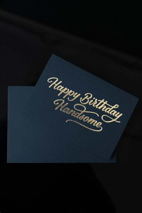 lifestyle image of Happy Birthday Handsome Greeting Card dark blue with gold writing with envelope on black table