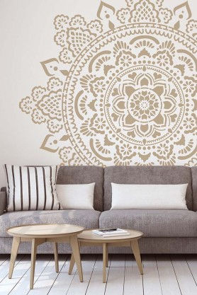 Holy Mandala Stencil For Walls & Floors in gold on the wall behind a sofa