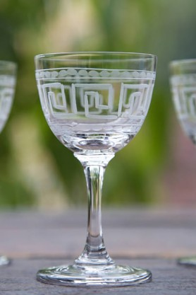 lifestyle image of Set Of 6 Vintage Style Crystal Liqueur Glasses - Greek Key on wooden table and garden setting background
