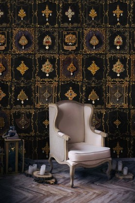 Lifestyle image of the dark shade of Anna's Jewellery wallpaper with chair in front of it