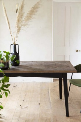 Close-up lifestyle image of the Parquet Wood Dining Table with pale floor and wall background with plant and black vase