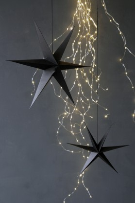 Image of the Set of 2 Black Star Decorations amongst fairy lights
