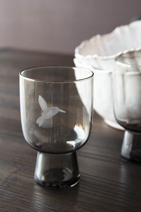 Lifestyle image of the Conical Stem Smoked Grey Engraved Bird Wine Glass on a table
