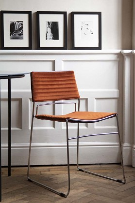 Lifestyle image of the front of the Chrome & Velvet Stackable Dining Chair In Rich Rust
