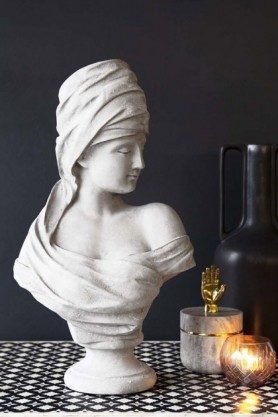 lifestyle image of Roman Greek Style Lady Bust - Stone Effect on patterned table with lit candle and black bottle neck vase with dark wall background