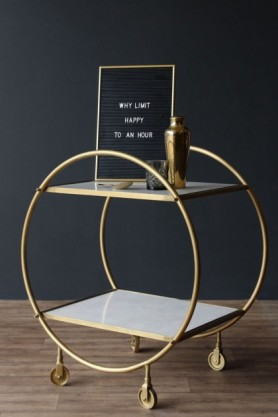lifestyle image of Round Brass and Marble Drinks Trolley with letter board and gold cocktail shaker on top on wooden flooring and dark wall background