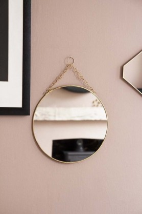 Lifestyle image of the Round Brass Hanging Bathroom Mirror hanging on pale wall with octagon mirror and picture frame