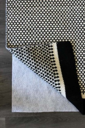 detail image of Rug Grip Mat - 120cm x 180cm with black and white rug on top and wooden flooring