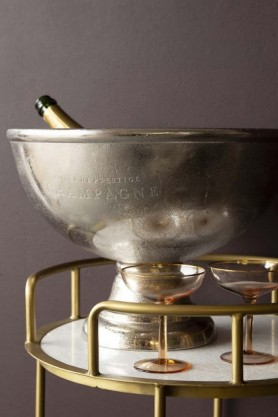 Lifestyle image of the Rustic Cuvee De Prestige Champagne Bowl on gold ad marble drinks trolley with bottle inside and dark wall background