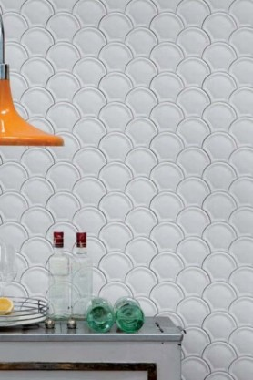 Lifestyle image of Scales Wallpaper with grey table wit bottles on and an orange ceiling light
