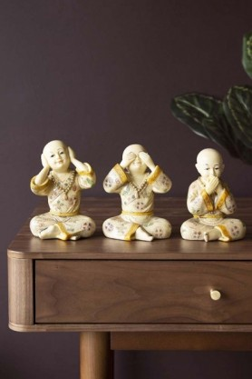 Lifestyle image of the Set Of 3 See No Evil, Hear No Evil, Speak No Evil Monks on wooden side table and dark wall background
