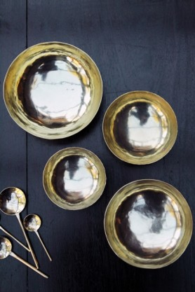 lifestyle image of Set Of 4 Handmade Brass Polished Bowls with gold spoons on black table