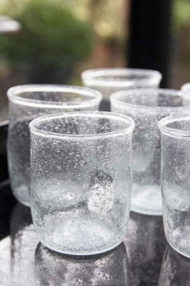 Close-up lifestyle shot of the clear set of 6 recycled glass water tumblers on black table with windows in background