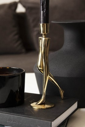 Lifestyle image of the Sexy Brass Legs Candle Holder stood on books on side table