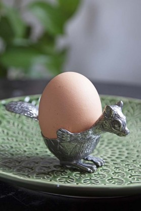 lifestyle Image of the Squirrel Silver Egg Cup with an egg in it on a green plate and plant in the background