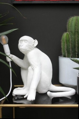 lifestyle image of Sitting Monkey Table Lamp - White on gold and glass table with cactus and dark wall background