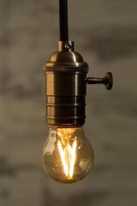 lifestyle image of E27 2W Small LED Bulb lit up with blurred brick wall background