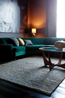 lifestyle image of Soumak Jute Rug - 4 Sizes Available - 5 Colours with green sofa and light turned on in background