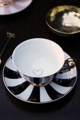lifestyle image of Stripy Teacup and Saucer Black/White with gold plate on black table