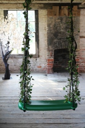 lifestyle image of Swing With The Plants - Green with rustic brick walls in background