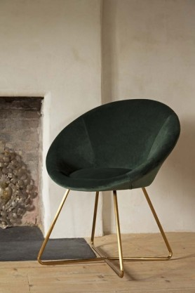 Homely lifestyle image of the The Grand Velvet Circular Dining Chair in Rich Green near fireplace and on wooden flooring with pale wall background