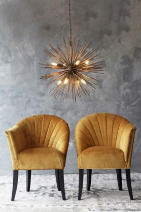 lifestyle image of The Lovers Velvet Chair - Golden Glow with gold star ceiling light above and grey wall background