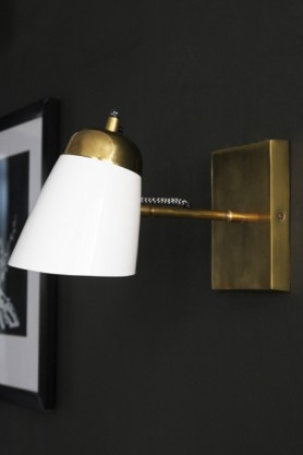 Lifestyle image of the white version of the The Mortimore Wall Light with black and white picture frame hung on dark wall background