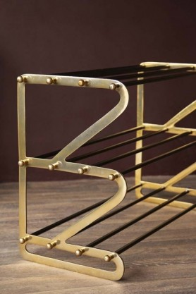 lifestyle image of the Three Tier Black & Brass Shoe Rack with no shoes on it on wooden flooring and dark purple wall
