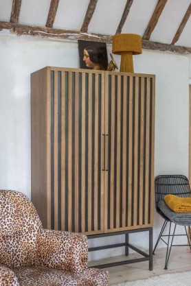Lifestyle image of the Timber Strips Shelved Storage Cabinet behind a Leopard Love Armchair