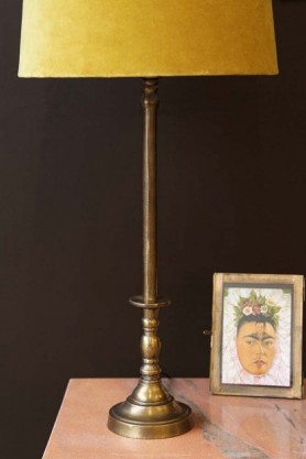 lifestyle image of Traditional Candlestick Style Antique Bronze Table Lamp Base with yellow shade on rose tinted marble side table and Frida Khalo picture with dark brown wall background